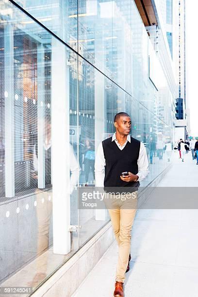 Professional man walking down city sidewalk