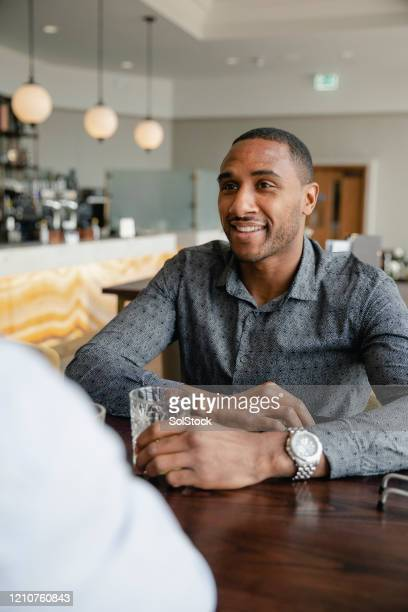 professional man with a drink, listening to friend in bar - one mid adult man only stock pictures, royalty-free photos & images