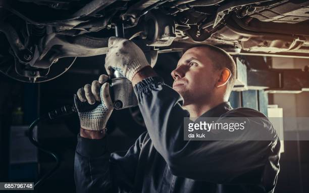 professional mechanic repairing a car in auto repair shop - auto repair shop stock pictures, royalty-free photos & images