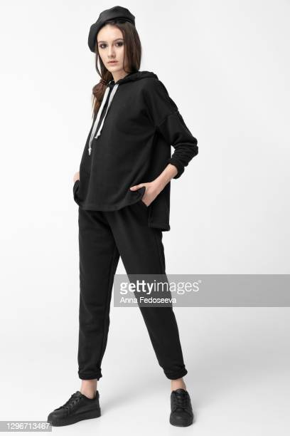 a professional model is dressed in black youth clothes. plain clothes. white background. beautiful girl. - vestimenta para mujer fotografías e imágenes de stock