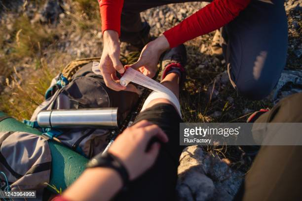 professional mountain climber bandaging his partner after an injury - bandage stock pictures, royalty-free photos & images