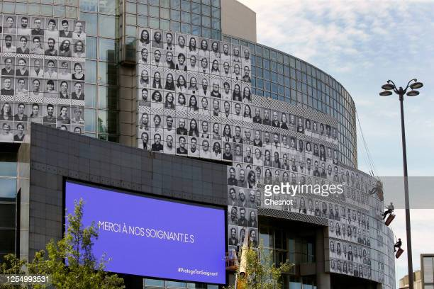 Professional mountaineers install posters featuring portraits of health workers on the facade of the Opera Bastille on July 08, 2020 in Paris France....