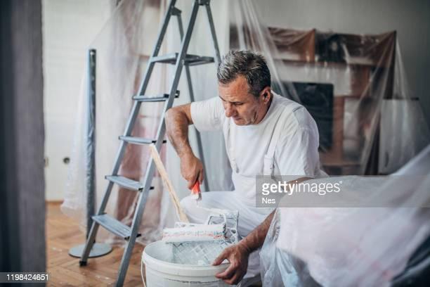 occupation professionnelle peignant des murs d'appartement - professional occupation photos et images de collection