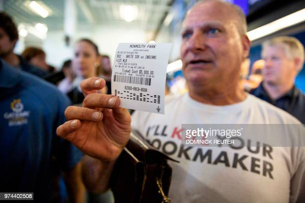 Professional oddsmaker Stu Feiner holds up a betting slip for $5000 USD on June 14 2018 after placing a bet at the Monmouth Park Sports Book on the...