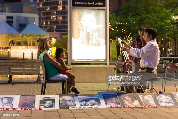 WEST TORONTO ONTARIO CANADA Professional painter making portrait of a woman and her child at Harbourfront Centre The woman is sitting in a pose with...
