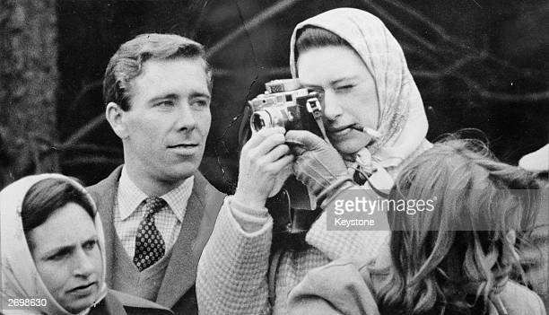 Professional photographer Antony ArmstrongJones the Earl of Snowdon watches critically as his fiancee Princess Margaret takes a snap at the Badminton...