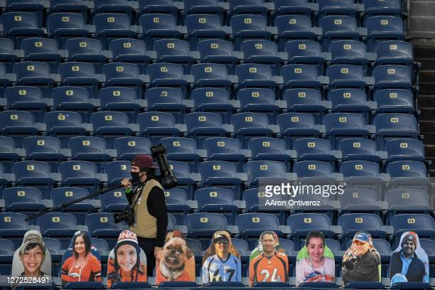 Professional photographer Dustin Bradford walks the stands behind cutouts of fans during the first quarter between the Tennessee Titans and the...