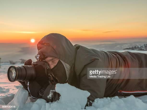 photographe professionnel couché dans la neige et de photographier le soleil couchant - photographe professionnel photos et images de collection