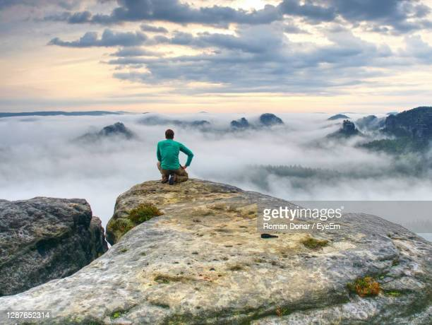 professional photographer on knees at tripod look into fall land and thinking. hiker with tripod - look back at early colour photography imagens e fotografias de stock