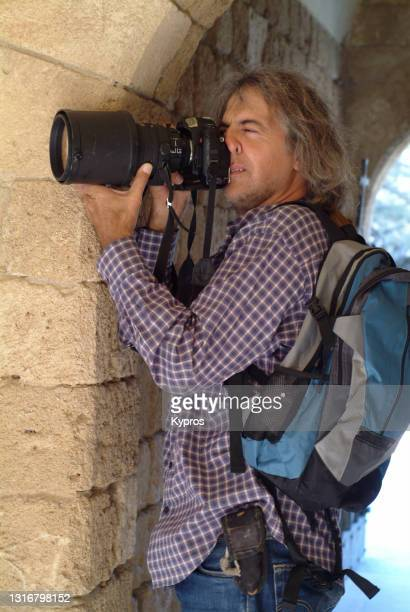 professional photographer using 35mm slr analogue film camera with 300mm f2.8 lens - photographer stock pictures, royalty-free photos & images