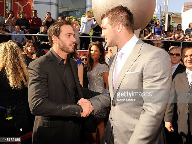 Professional racing driver Jimmie Johnson and NFL player Tim Tebow of the New York Jets shake hands as they arrive at the 2012 ESPY Awards at Nokia...
