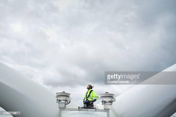 professionele technicus die van de kabeltoegang zich op dak (hub) van windturbine tussen bladen en antennes bevindt en omhoog op het blad kijkt. dramatische hemel achter. handen op heupen - industriële apparatuur stockfoto's en -beelden