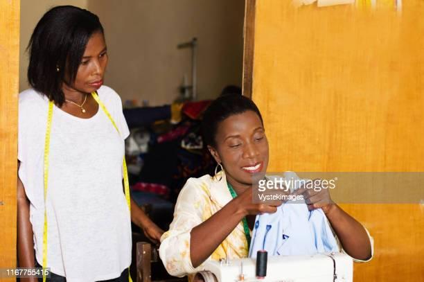professional seamstress sews and student notes. - femme ivoirienne photos et images de collection