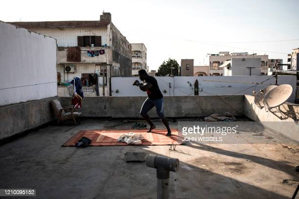 Professional Senegalese wrestler, Moussa Diop , shadow boxes on his rooftop in Dakar on April 15, 2020. - Professional Senegalese wrestlers would...