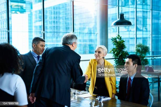 professional senior woman shaking hands with male colleague - yellow coat stock pictures, royalty-free photos & images