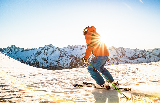 Professional skier athlete skiing at sunset on top of french alps ski resort - Winter vacation and sport concept with adventure guy on mountain top riding down the slope - Warm bright sunshine filter 1063553400