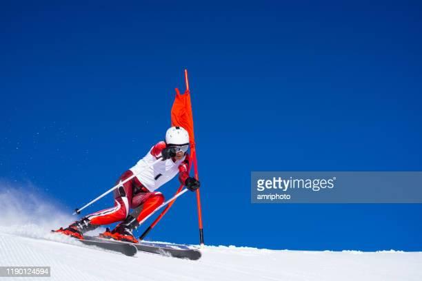 skieur professionnel sur le cours de super g au ciel bleu clair - événement sportif d'hiver photos et images de collection