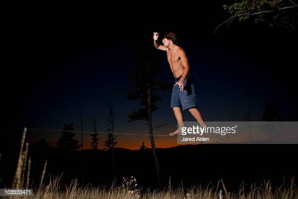 A professional slackliner plays around on the slackline in a field at sunset in the Blue Mountain of Missoula, Montana.