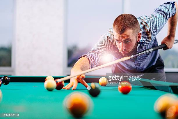 Professional snooker player aiming balls