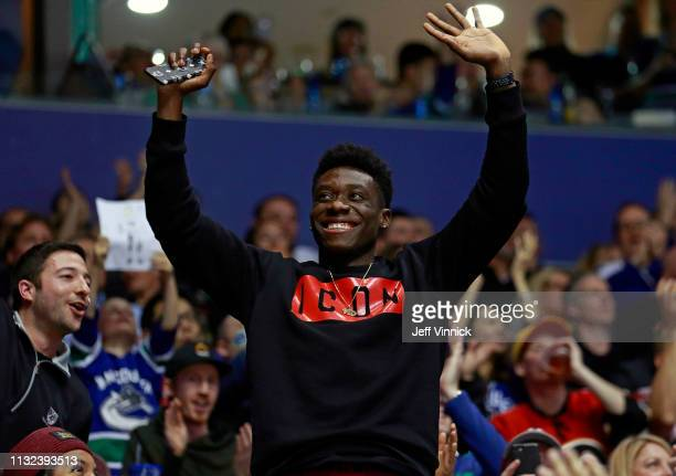 Professional soccer player Alphonso Davies waves to the crowd during the NHL game between the Vancouver Canucks and the Calgary Flames at Rogers...