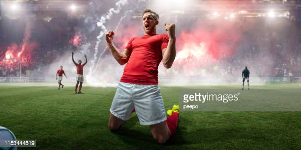 professional soccer player celebrating on knees in stadium with flares - stadium stock pictures, royalty-free photos & images