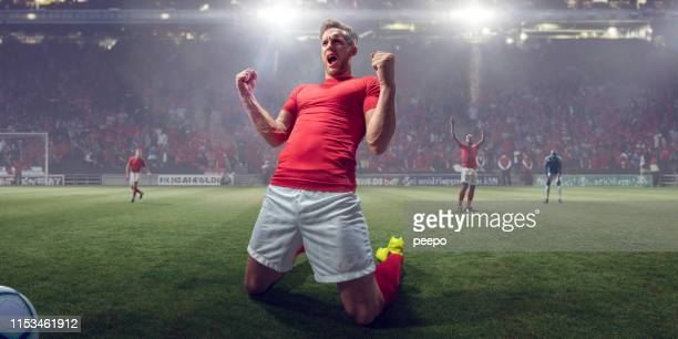 professional soccer player celebrating victory on knees with fists clenched - football player stock pictures, royalty-free photos & images
