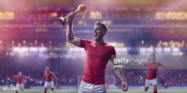 professional soccer player holding up gold trophy in victory celebration - cup stock pictures, royalty-free photos & images
