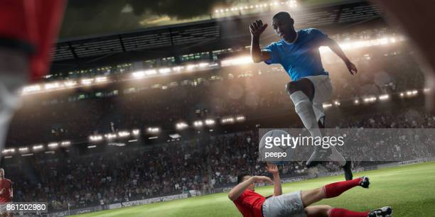 professional soccer player jumping over rival player during football match - football player stock pictures, royalty-free photos & images