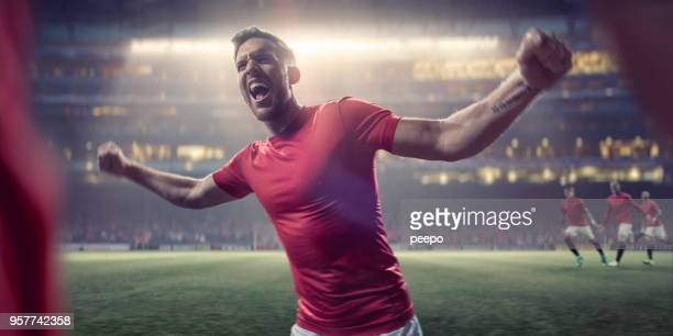 professional soccer player with arms out shouts in victorious celebration - football player stock pictures, royalty-free photos & images
