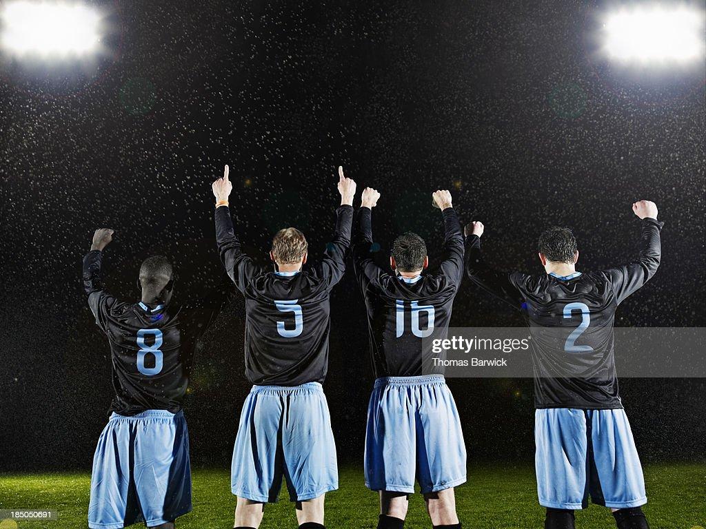 Professional soccer teammates celebrating on field : Stock Photo