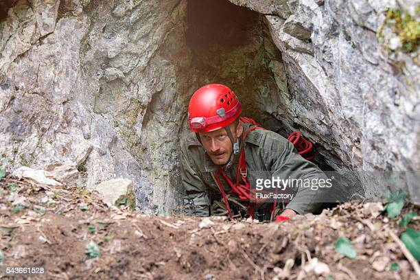 professional speology male leaves the cave-pit