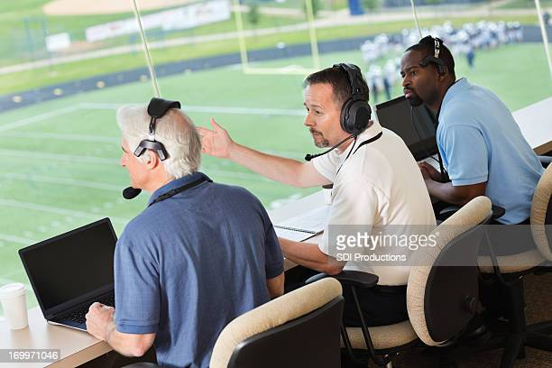 professional sports commentators in press box at football game - commentator stock pictures, royalty-free photos & images