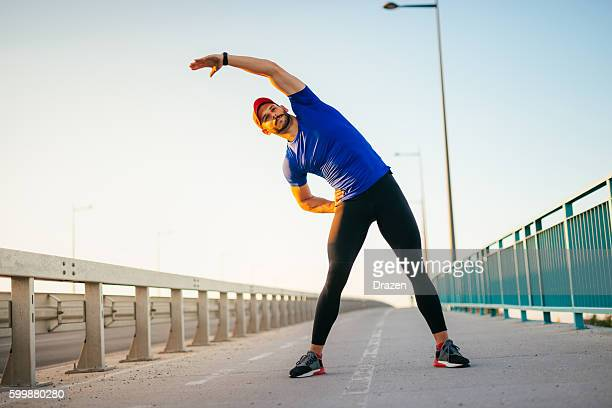 professional sportsman preparing for outdoor training - warming up stock pictures, royalty-free photos & images