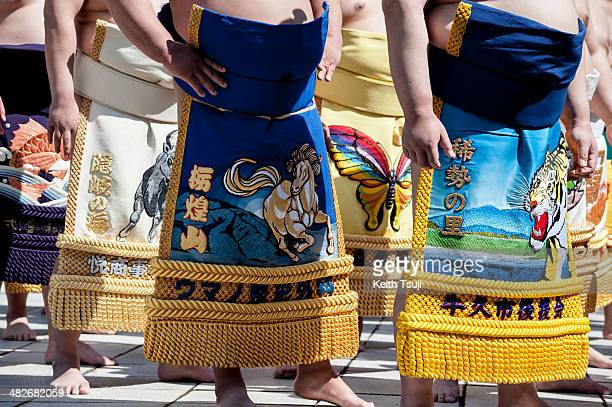 Professional sumo wrestlers with Keshomawashi large apron are seen during the Ceremonial Sumo Tournament or Honozumo at the Yasukuni Shrine on April...