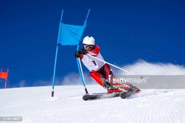 skieur professionnel de super g près du drapeau bleu de poteaux - événement sportif d'hiver photos et images de collection