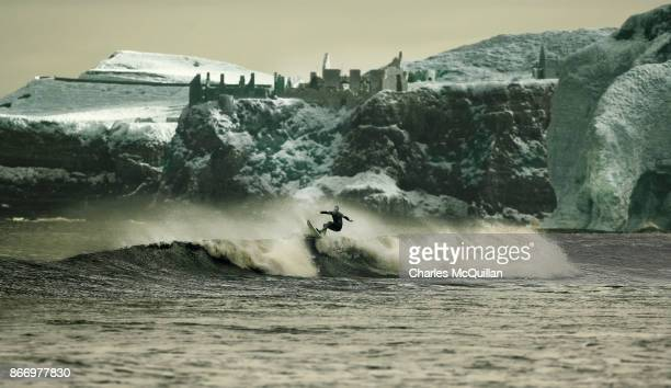 Professional surfer Al Mennie catches a wave under the famous Dunluce castle ruins on October 27 2017 in Portrush Northern Ireland Mennie spends his...