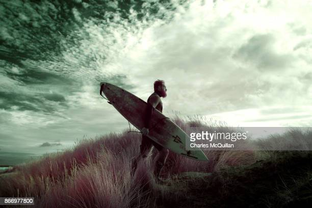 Professional surfer Al Mennie walks over sand dunes as he makes his way back to his van after surfing on October 27 2017 in Portrush Northern Ireland...