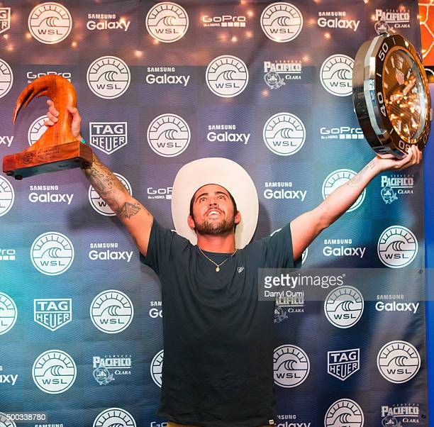 Professional surfer Billy Kemper celebrates after accepting the trophy and TAG Heuer watch for his first place finish at the 'TAG Heuer And World...