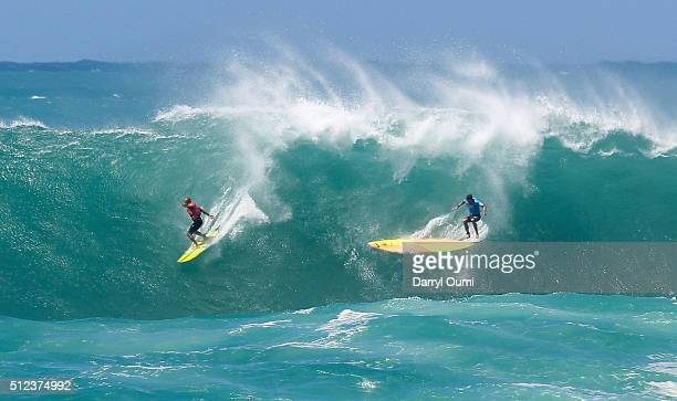 Professional surfer Ramon Navarro makes the drop on a wave while professional surfer Jamie Mitchell loses control and wipes out at Waimea Bay on...