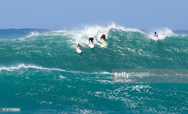Professional surfers Grant Baker Ross ClarkeJones and Kelly Slater attempt to catch a wave in the second round of The Quiksilver in Memory of Eddie...