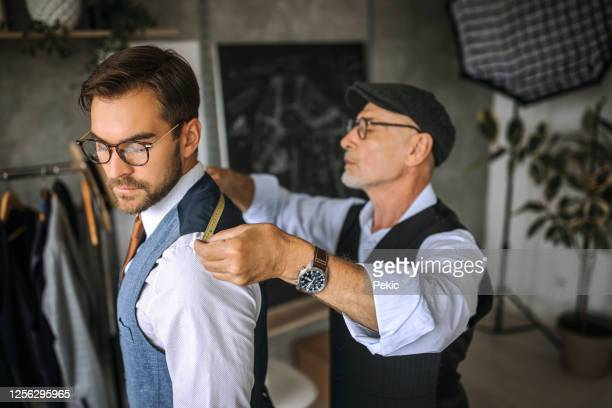 professional tailor taking back measurements for a suit - customized stock pictures, royalty-free photos & images