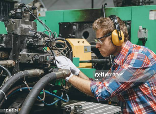 professional technical worker man working with production line machine - ear protection stock pictures, royalty-free photos & images