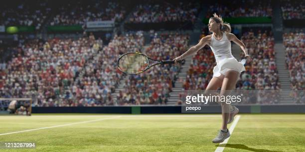 professional tennis player in mid motion after serving on grass - serving sport stock pictures, royalty-free photos & images