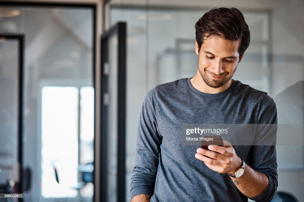Professional using mobile phone at office : Stock Photo