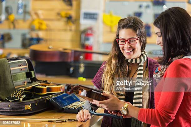 Professional violinist has violin repaired in musical instrument repair shop