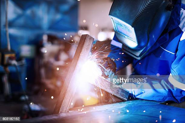 professional welder in a factory welding steel bars - stahl stock-fotos und bilder