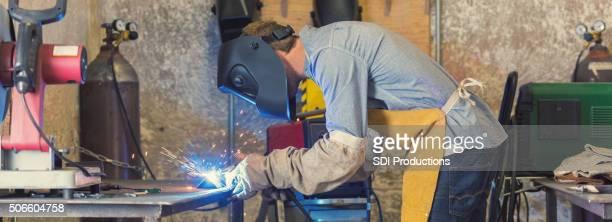 Professional welder using metal torch in workshop