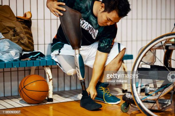 professional wheelchair basketball player putting on his - differing abilities fotografías e imágenes de stock
