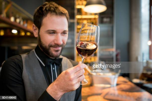Professional wine taster at a wine cellar looking at the color of the wine smiling