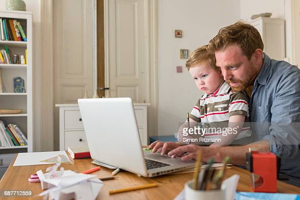 professional with toddler son working at home - stay at home father stock pictures, royalty-free photos & images